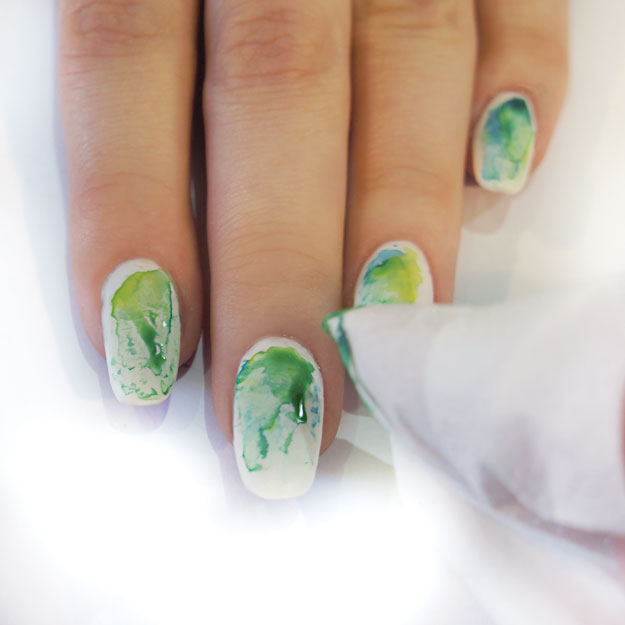 Dab off excess paint and water with a tissue paper. | How to do Aquarelle Nail Art, the Newest Nail Art Trend; check out the how-to at http://www.nailpro.com/aquarelle