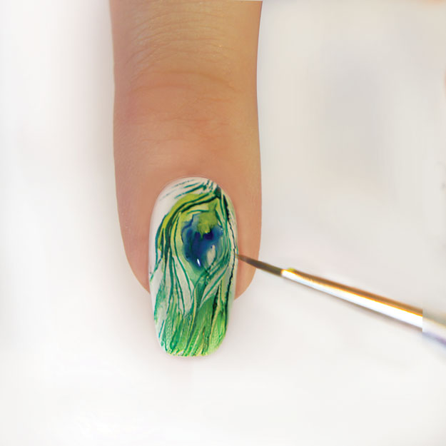 Paint a dark blue half moon onto the center of the feather. | How to do Aquarelle Nail Art, the Newest Nail Art Trend; check out the how-to at http://www.nailpro.com/aquarelle